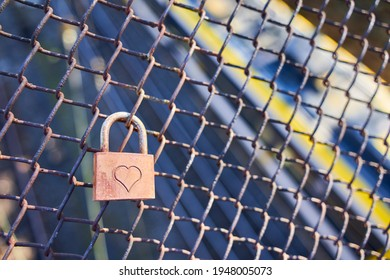 Lovelock ( Liebesschloss ) fixed to an old rusty wire mesh fence, heart shape can be seen on the weathered metal. A train passes by, motion blurred. Top view. Close up.