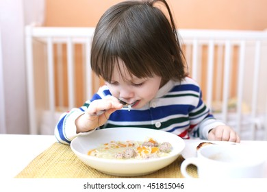 Lovely 2 years boy eating soup