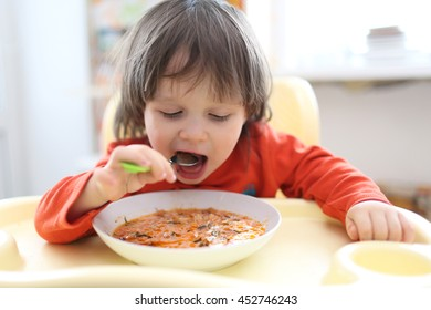lovely 2 years boy eating soup red-beet soup