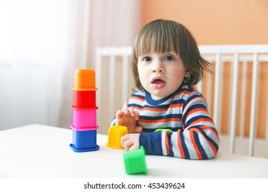 lovely 2 years toddler playing plastic blocks