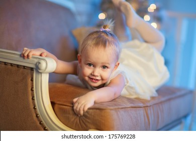 A lovely 3 year old girl in a beautiful white dress lying on a sofa and imagining herself as a gymnast