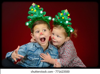 lovely and adorable brother and sister family portrait in christmas style trees