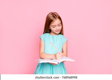 Lovely adorable charming little girl is looking down at the copybook in her hands and writing information there, she is wearing light blue dress, isolated on bright pink background, copyspace