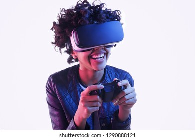 Lovely African American teen girl using controller and laughing while standing on white background and playing VR game