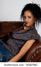 Lovely African American woman happy and reclining on a couch