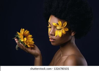 Lovely African woman with a sunflower and creative makeup on her face