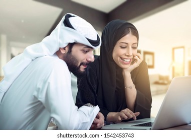 lovely Arabic Couple sitting using laptop looking for new house.