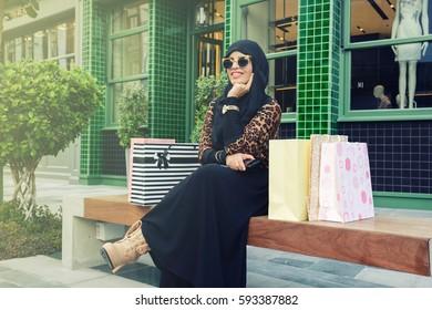 lovely arabic woman wearing abaya and hijab with shopping bags, arabic woman fashion
