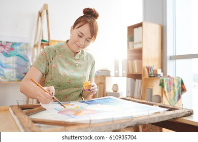 Lovely artist painting in her workshop
