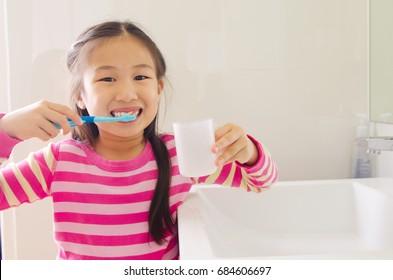 Lovely asian child brushing teeth in the bathroom