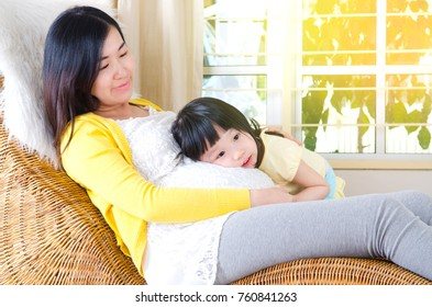 Lovely asian child listening to her pregnant mother's stomach
