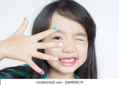 lovely asian child show her painted nails  on white background