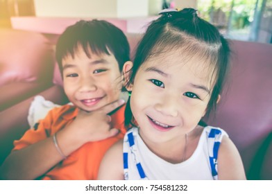 Lovely asian children relaxing at home. Brother and sister smiling with bright sunlight. Happy family spending time together, loving and bonding of sibling. Vintage film effect.