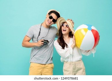 Lovely Asian couple in summer casual clothes and beach accessories studio shot isolated on light blue background