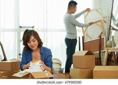 Lovely Asian couple wrapped up in unpacking moving boxes while gathered together in messy living room of new apartment