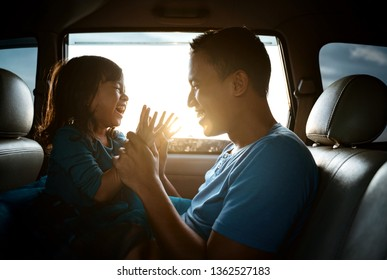 lovely asian daughter with father in the car playing together laughing