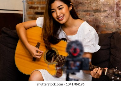 Lovely Asian female smiling and playing cover song while sitting on couch in front of video camera