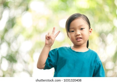 Lovely asian girl smiling and showing thump up for fight on sign with bokeh background. Adorable baby (four years) giving you two fingers as symbol from her hand (mean of keep going, don't give up)