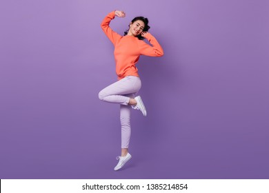 Lovely asian girl standing on one leg. Full length view of attractive stylish japanese woman jumping on purple background.