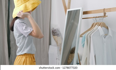 Lovely Asian girl trying the colorful dress in front of the mirror