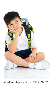 Lovely asian school boy sitting on the floor and having a thought