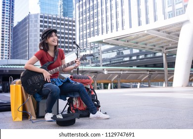 Lovely Asian street girl musician playing guitar for donation on the sidewalk in city against city scape as background