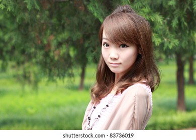 A lovely asian woman in a park' grass plot.