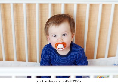 lovely baby age of 1 year with pacifier in white bed