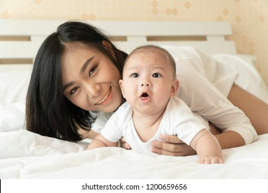 Lovely baby asian boy lying with mother in bedroom. A portrait of healthy 5 month asian baby looking and smile with black eyes and short hair. Good healthy, Mother's Day, Children day concept.