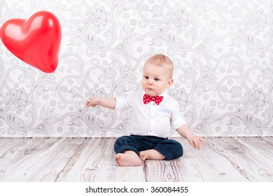 Lovely baby boy playing with red heart shaped balloon