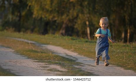 Joli bébé courant sur une route poussiéreuse, enfant jouissant de la vie, ralenti