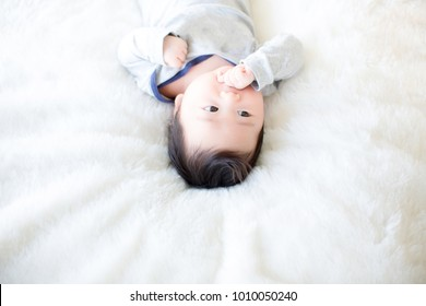 Lovely baby putting his hands in his mouth. image for background, wallpaper, copy space, fashion and article. Infectious disease in babies, hand foot and mouth diseases. Prevention of diseases infants