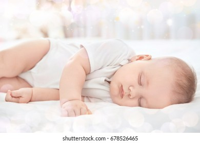 Lovely baby sleeping on bed and blurred lights on background