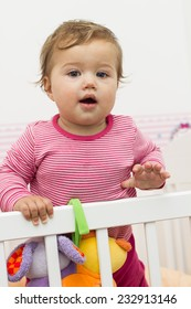 Lovely baby standing in crib.
