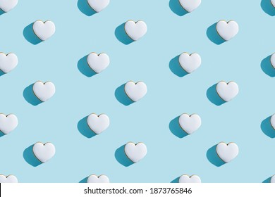 Lovely bakery pattern. Festive pastry design. Holiday celebration. Decorated white icing gingerbread heart figure cookies isolated on blue pastel.