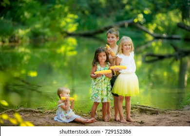 Lovely barefooted children in the woods eating corn