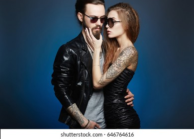 lovely beautiful couple in sunglasses.bearded Hipster boy and beauty girl with tattoo over blue background