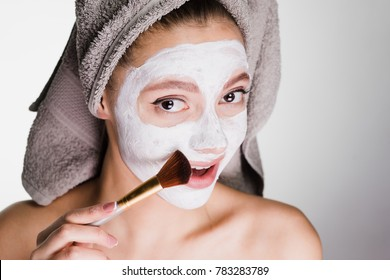lovely beautiful girl with a towel applied a white nutritious mask to her face with a brush