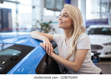 Lovely beautiful happy woman leaning on a new automobile at the dealership, looking away happily smiling, copy space. Dreamy woman posing with her new car. Female dreaming of travelling adventures