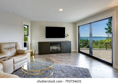 Lovely beige family room with leather sofa, glass top cocktail table, TV Stand with Electric Fireplace and glass sliding doors leading to a sunny deck.