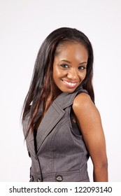 Lovely black, African American woman  wearing  grey vest looking at the camera with a happy and friendly smile