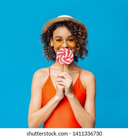 Lovely black girl eating big colorful lollipop, blue studio background
