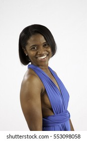 Lovely Black woman in a blue dress, smiling at the camera over her shoulder
