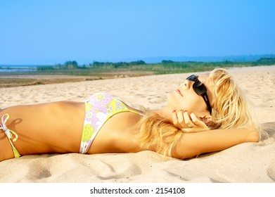 lovely blond in bikini tanning at the beach