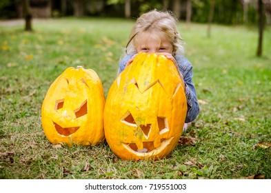 lovely blond girl hiding behind orange autumn pumpkins in the garden