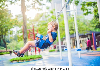 Lovely blond little boy on a swing in the park. Adorable boy having fun at the playground.