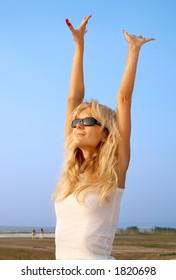 lovely blond raising hands to the sun