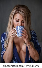 Lovely blonde girl sits posing on the couch and drinks coffee