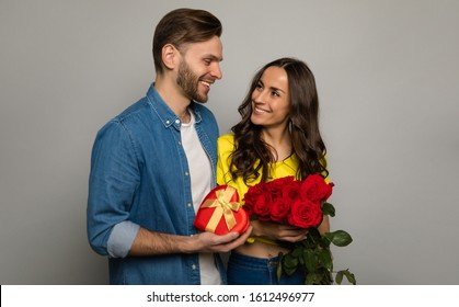 Lovely box. Close-up photo of a handsome man, who is giving a present and a bouquet of red roses to his girlfriend, while looking into her happy eyes.