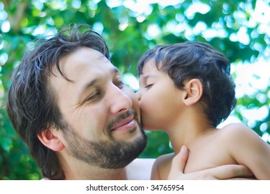 Lovely boy and his father holding him in hands in nature